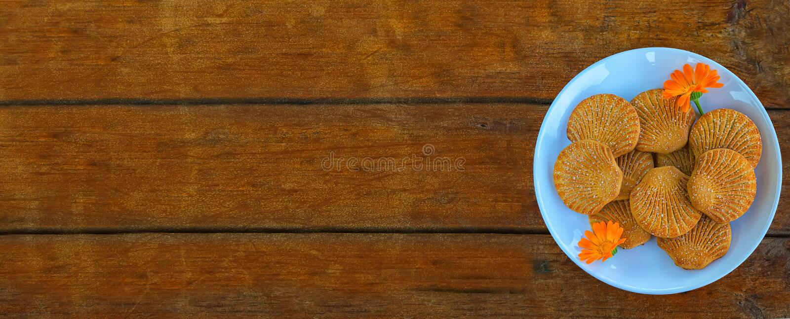 Shells sugar cookies in a blue plate with calendula flowers on wooden background, long format. Banner.  stock images