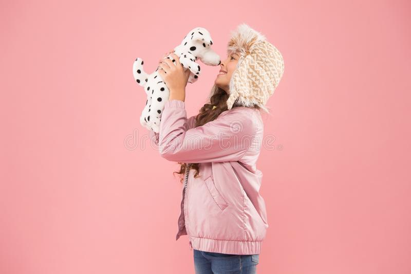 Shelter for animals. Dalmatian dog. Games kids play. Happy small smiling child play with soft dog on pink background royalty free stock photography
