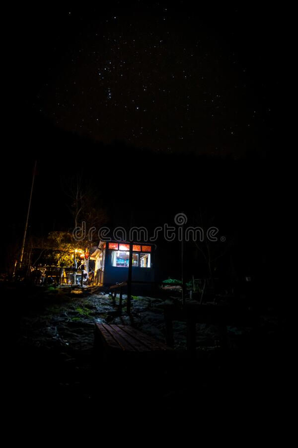 Cabin in nature with stars. Shelter; cabin in nature with lights on and no person, forest and stars on the background and bench with table in front. Escapism royalty free stock photo