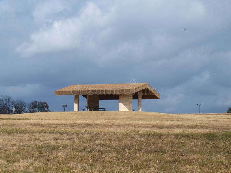 Shelter House On Hill. This shelter house sits on a hill top overlooking a lake below. The threatening clouds is a part of a polar vortex that is only moments stock photography