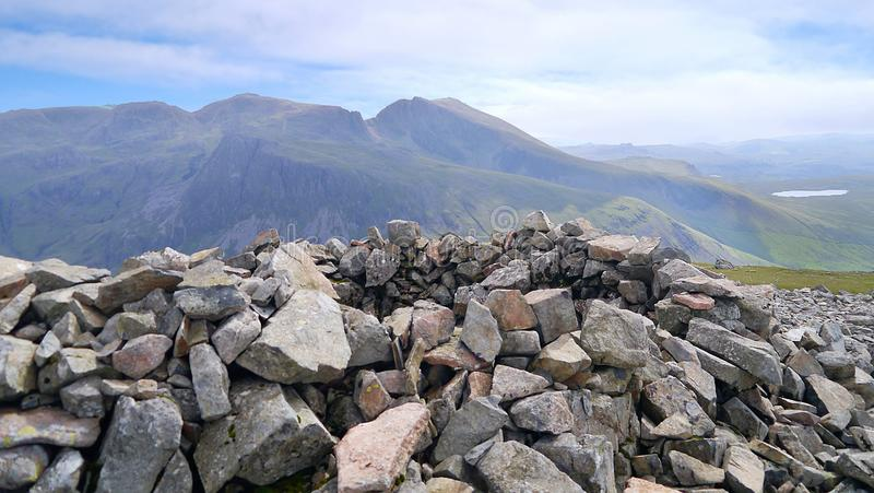 Shelter on Kirk Fell with the Scafells at the back. Widescreen view of Sca Fell on the right over there with it`s slightly higher neighbour Scafell Pike left of stock photography