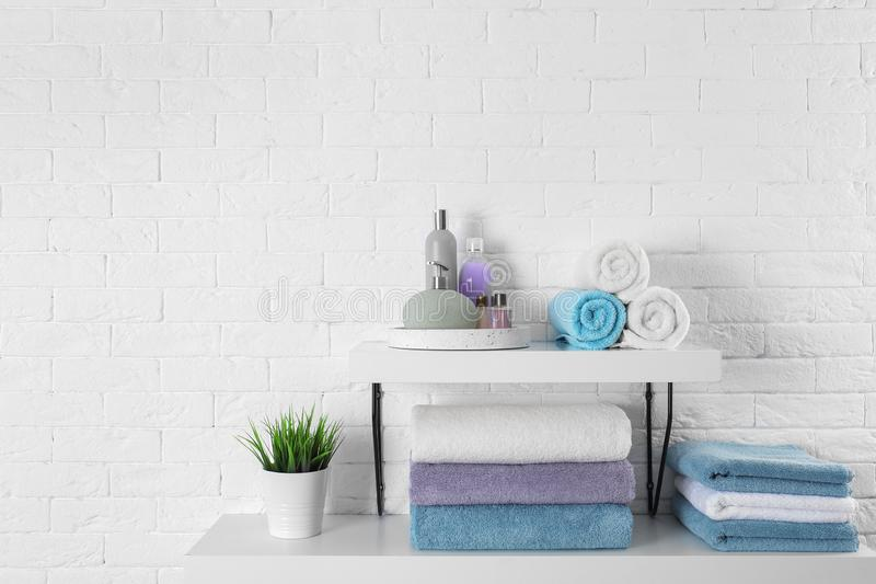 Shelves with clean towels and toiletries on brick wall. Space for text stock images
