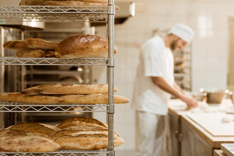 Shelves with fresh bread and blurred baker on background. At baking manufacture stock photography