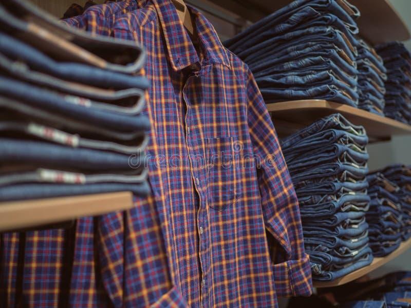 Shelves jeanswear. Retro Plaid shirt on the background of denim royalty free stock photos