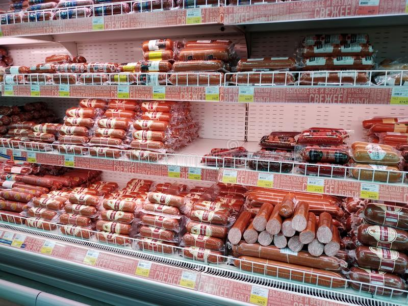 Shelves with large assortment of various smoked sausage in a hypermarket Lenta stock photos