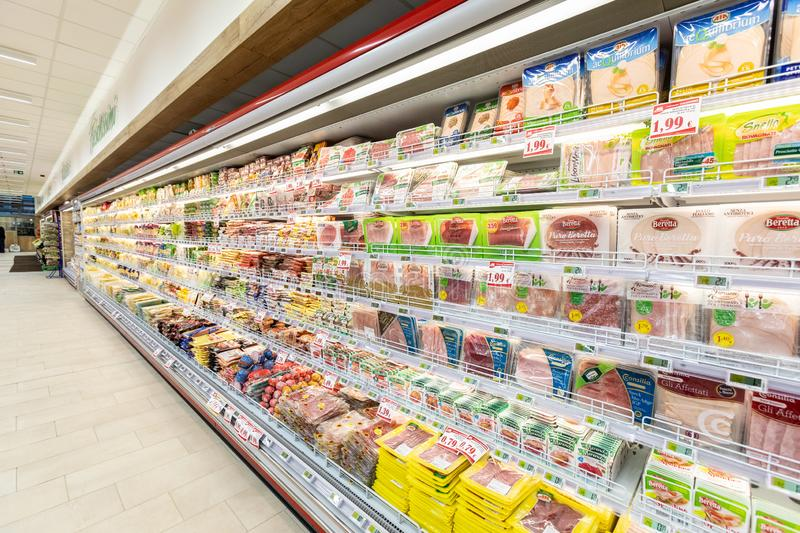 Shelves of a long refrigerator with products. Sliced under vacuum. stock images