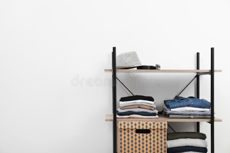 Shelves unit with stacked clothes and  near white wall. Space for text. Shelves unit with stacked clothes and box near white wall. Space for text royalty free stock images