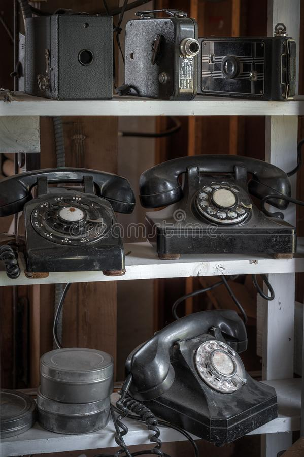 Shelves of Vintage Phones Cameras and Film Canisters. Dirty and grungy stock images