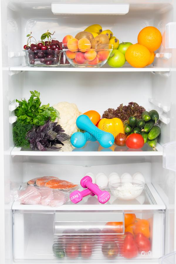 On the shelves of a white refrigerator, a stock of fresh vegetables, fruits, berries, fish, meat, eggs, cottage cheese, as well as. Pink and blue dumbbells for royalty free stock photography