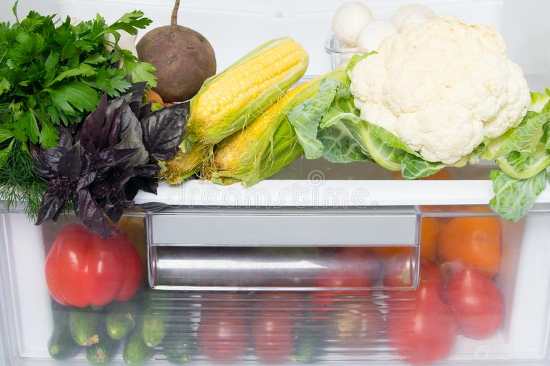 On the shelves of a white refrigerator, a stock of fresh vegetables, tomatoes, cucumbers, corn, mushrooms, greens, cauliflower and. Beets, close-up stock image