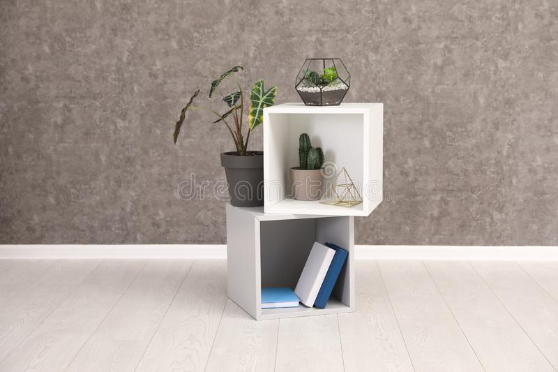 Shelving unit with indoor plants and books for interior design on floor at grey wall. Trendy decor stock photo