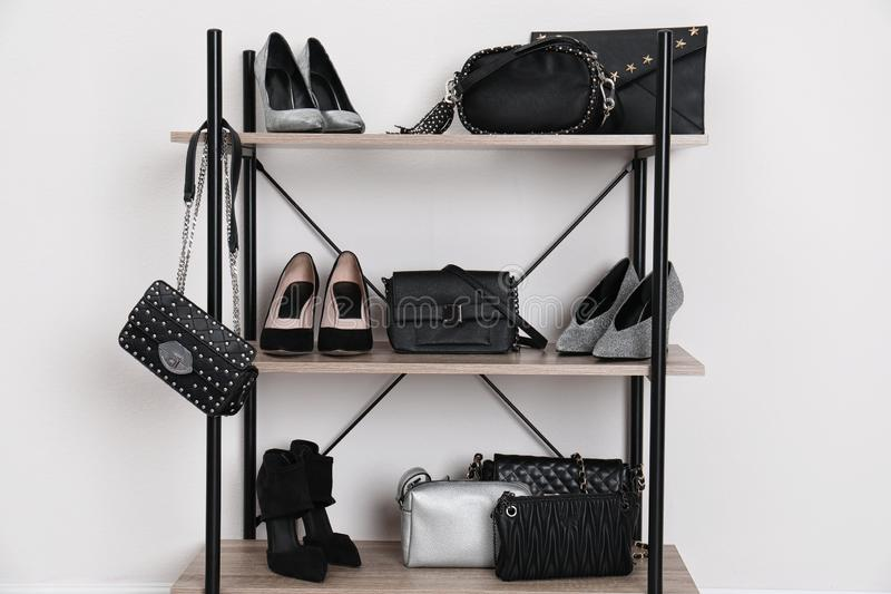 Shelving unit with stylish shoes and purses near white wall. Element of dressing room royalty free stock images