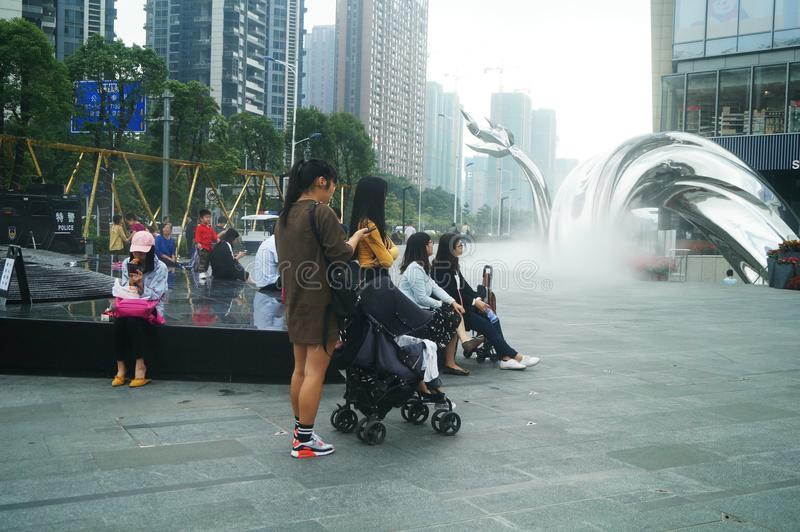 Shenzhen, China: adults and children play around the fountain in the shopping mall. In the morning, Yi Fang Cheng shopping mall fountain pool, adults and stock photo
