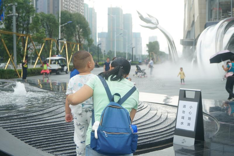Shenzhen, China: adults and children play around the fountain in the shopping mall. In the morning, Yi Fang Cheng shopping mall fountain pool, adults and stock photos