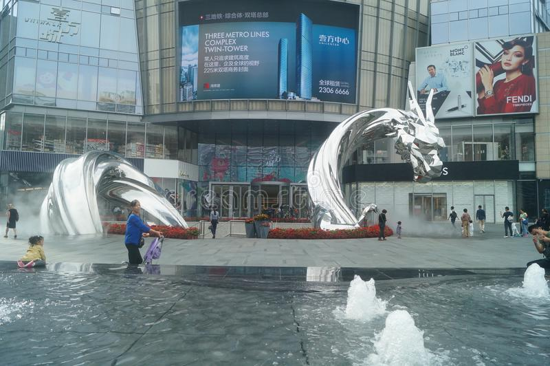 Shenzhen, China: adults and children play around the fountain in the shopping mall. In the morning, Yi Fang Cheng shopping mall fountain pool, adults and stock image
