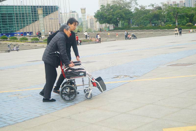 Shenzhen, China: as mulheres idosas nas cadeiras de rodas praticam andar imagem de stock