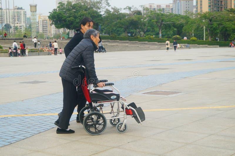 Shenzhen, China: bejaarden in rolstoelen praktijk het lopen stock foto's