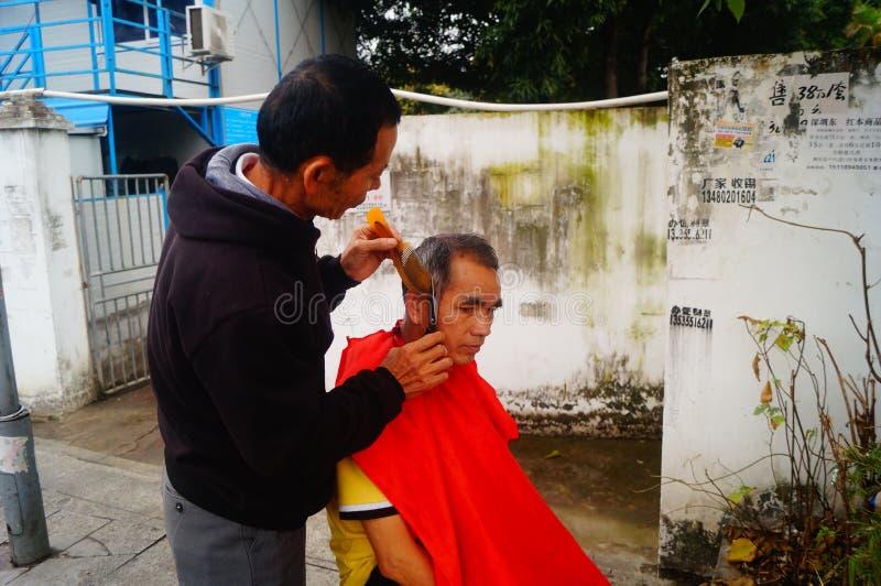 Shenzhen, China: de kapper is op de straat, is de last goedkoop stock afbeelding
