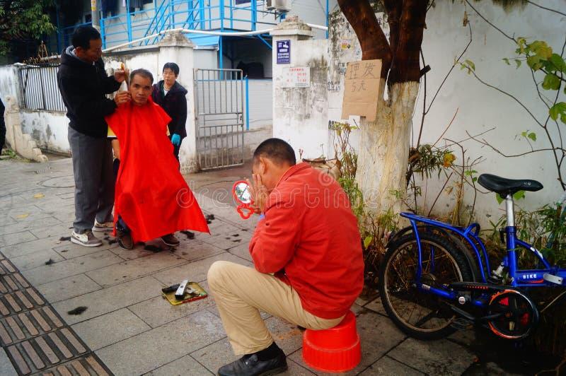 Shenzhen, China: de kapper is op de straat, is de last goedkoop stock foto