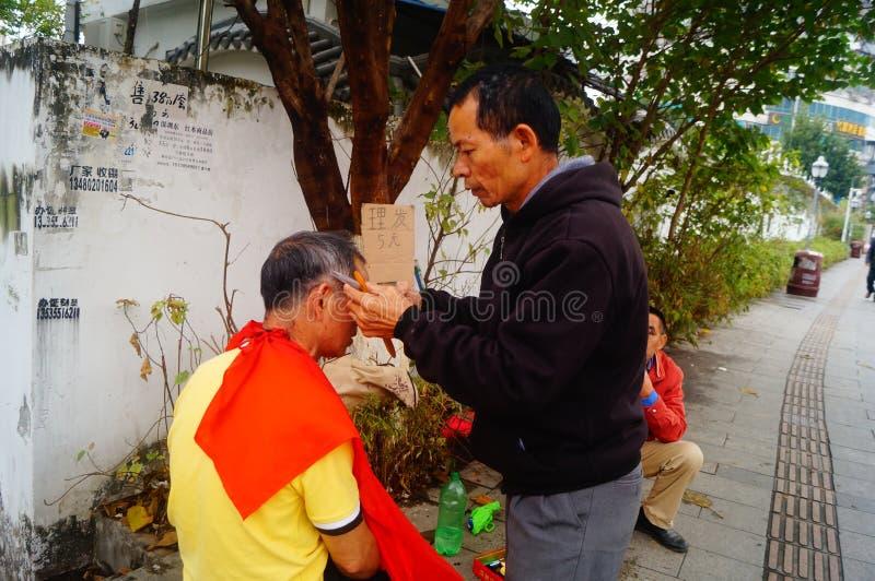 Shenzhen, China: de kapper is op de straat, is de last goedkoop royalty-vrije stock afbeelding