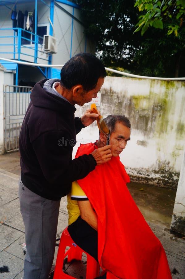 Shenzhen, China: de kapper is op de straat, is de last goedkoop royalty-vrije stock foto