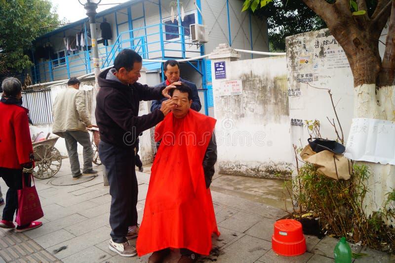 Shenzhen, China: de kapper is op de straat, is de last goedkoop royalty-vrije stock foto's