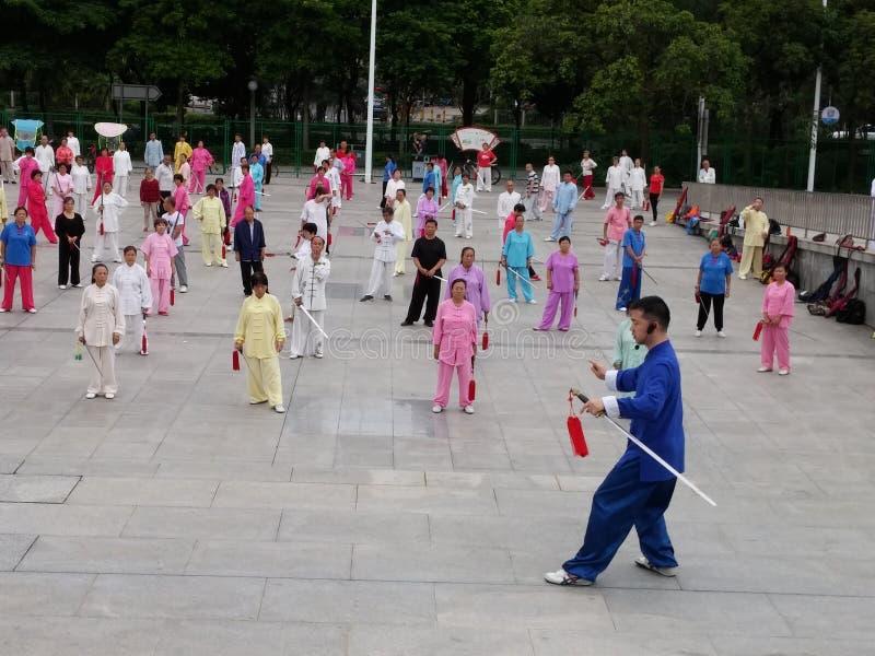 Shenzhen, China: in de ochtend, op middelbare leeftijd en bejaarden en vrouwen leer tai chizwaard opleiding in het vierkant stock afbeeldingen