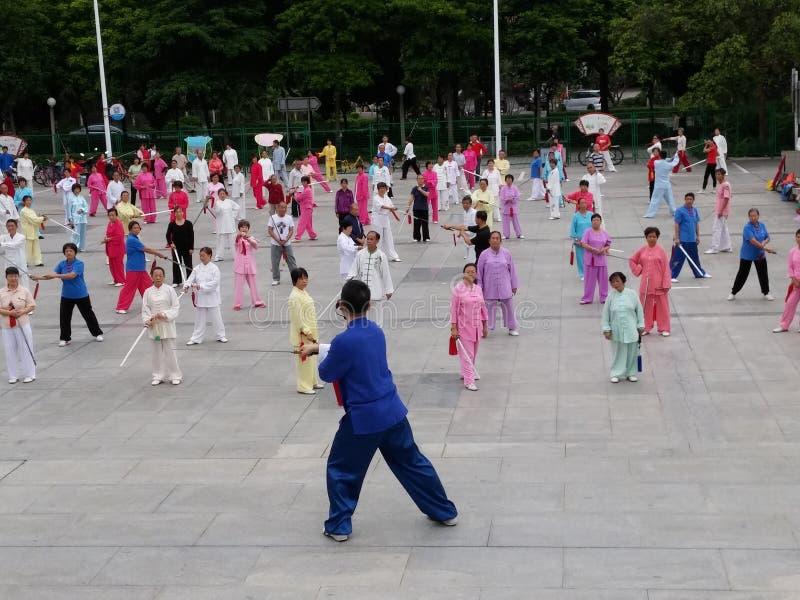 Shenzhen, China: in de ochtend, op middelbare leeftijd en bejaarden en vrouwen leer tai chizwaard opleiding in het vierkant stock afbeelding