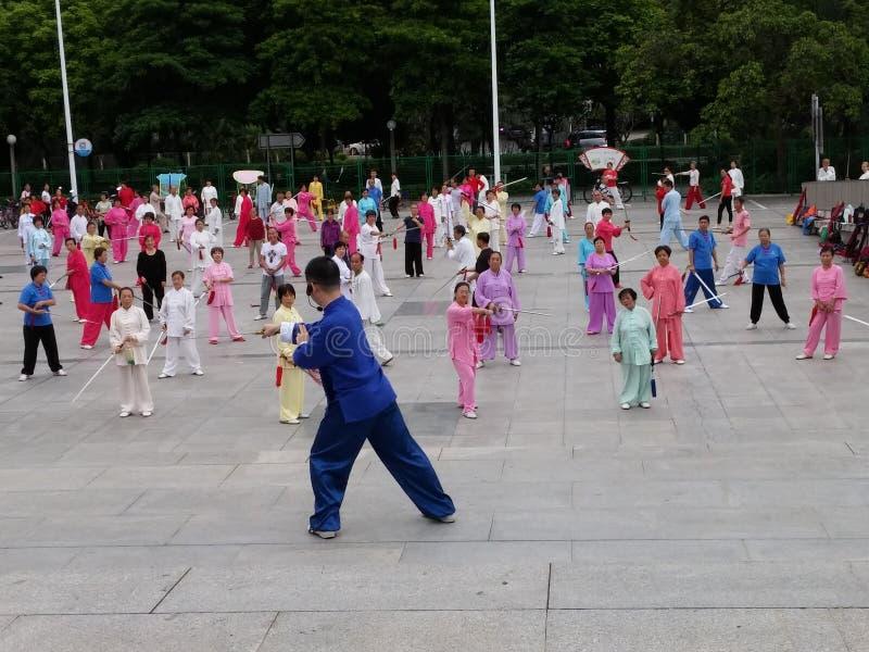 Shenzhen, China: in de ochtend, op middelbare leeftijd en bejaarden en vrouwen leer tai chizwaard opleiding in het vierkant stock fotografie