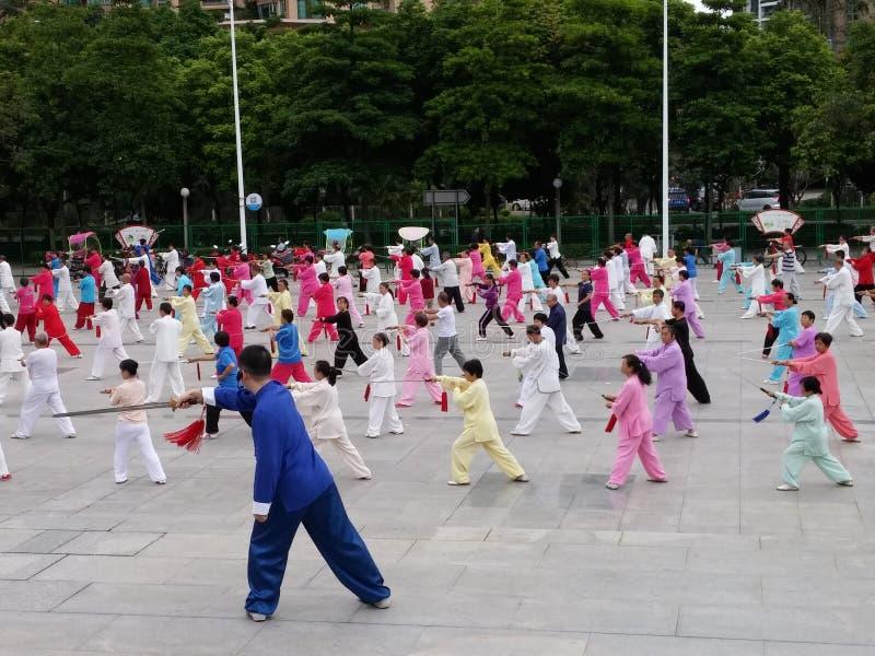 Shenzhen, China: in de ochtend, op middelbare leeftijd en bejaarden en vrouwen leer tai chizwaard opleiding in het vierkant stock foto's