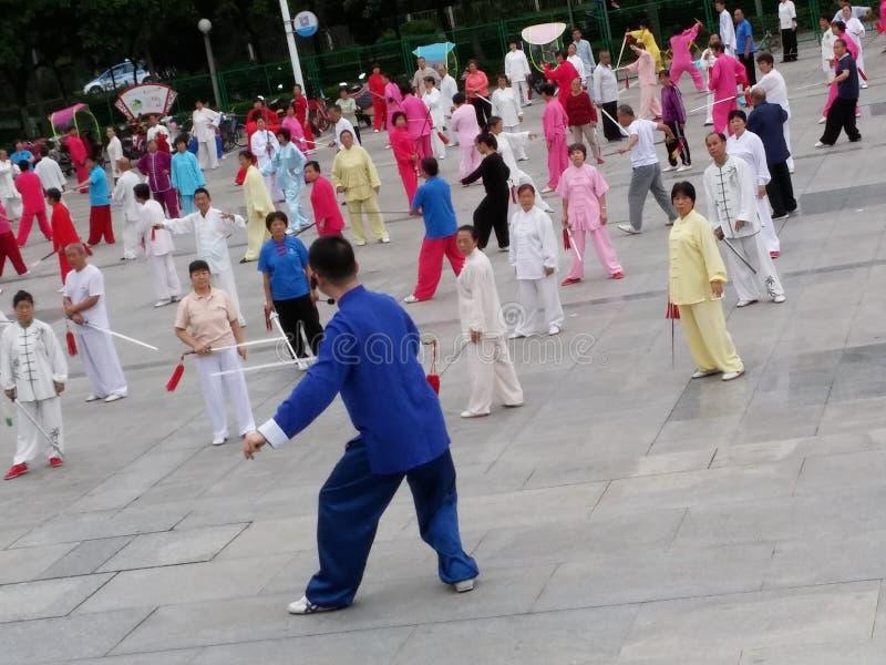 Shenzhen, China: in de ochtend, op middelbare leeftijd en bejaarden en vrouwen leer tai chizwaard opleiding in het vierkant royalty-vrije stock afbeelding