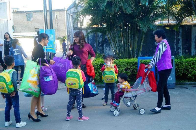 Shenzhen, China: eine junge Mutter nimmt ihr Kinderhaus vom Kindergarten lizenzfreies stockbild