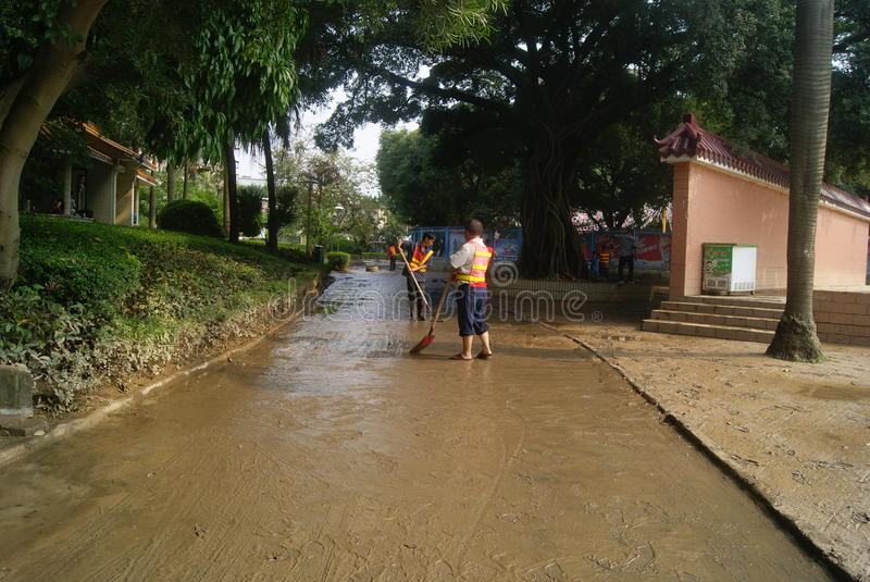 Shenzhen, China: Eradicate road mud. Shenzhen Baoan Xixiang Park, heavy rain caused the flood disaster, flood, the road is full of mud. Several workers are to royalty free stock image