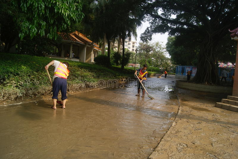 Shenzhen, China: Eradicate road mud. Shenzhen Baoan Xixiang Park, heavy rain caused the flood disaster, flood, the road is full of mud. Several workers are to royalty free stock photos