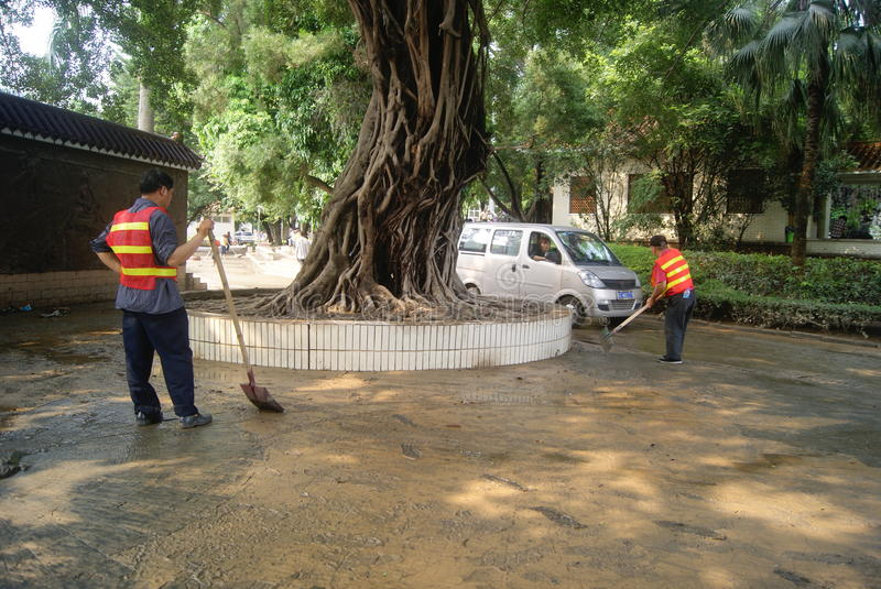 Shenzhen, China: Eradicate road mud. Shenzhen Baoan Xixiang Park, heavy rain caused the flood disaster, flood, the road is full of mud. Several workers are to stock image