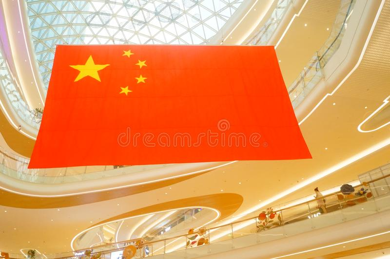 Shenzhen, China: a giant five-star red flag hangs in a shopping mall to greet National Day stock photography