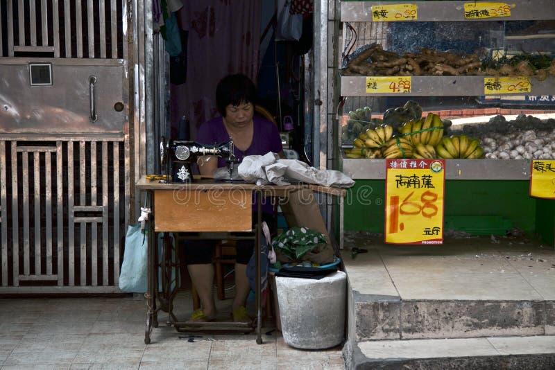 SHENZHEN, CHINA, 24 JULI 2011: Het Chinese vrouw naaien met haar naait stock afbeelding