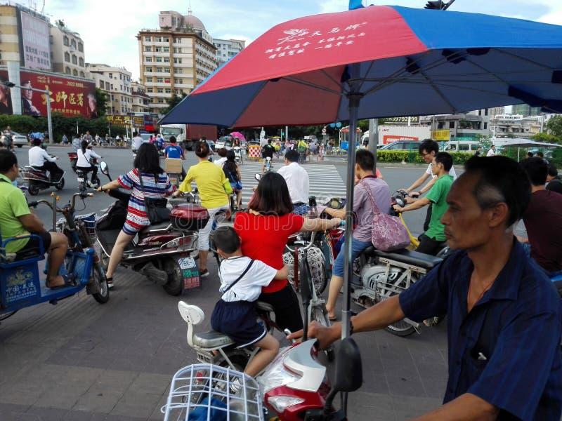 Shenzhen, China: las madres llevan a niños en las bicicletas eléctricas en los empalmes del tráfico fotos de archivo