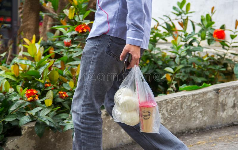 Yuong man carrying snacks of coffee and bread in throw-away plastic shopping bags. royalty free stock photography