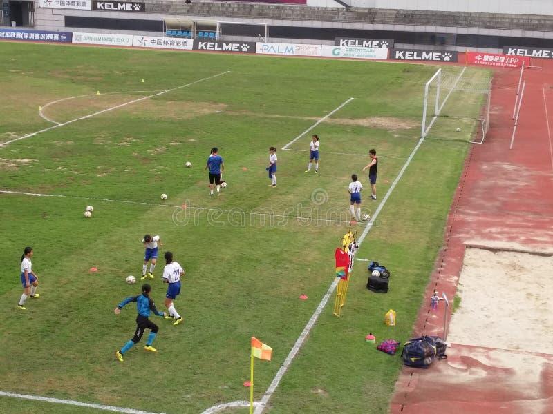 Shenzhen, China: os adolescentes treinam para jogar o futebol imagens de stock