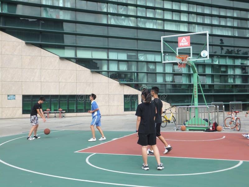 Shenzhen, China: os meninos e as meninas jogam o basquetebol no campo de básquete do estádio foto de stock royalty free