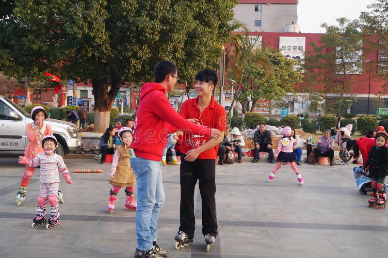 Shenzhen, China: outdoor skating. Shenzhen Baoan Xixiang, outdoor plaza, a little girl and her teacher in skating. This is the recreational sports, people like stock photography