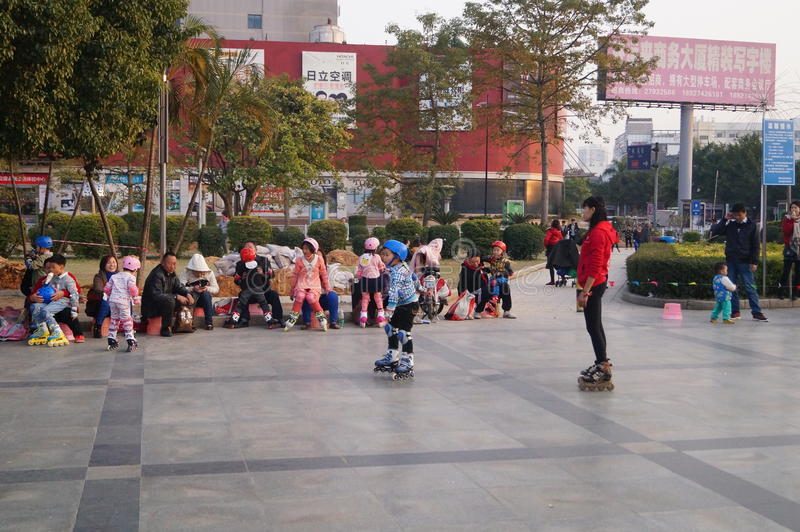 Shenzhen, China: outdoor skating. Shenzhen Baoan Xixiang, outdoor plaza, a little girl and her teacher in skating. This is the recreational sports, people like royalty free stock image