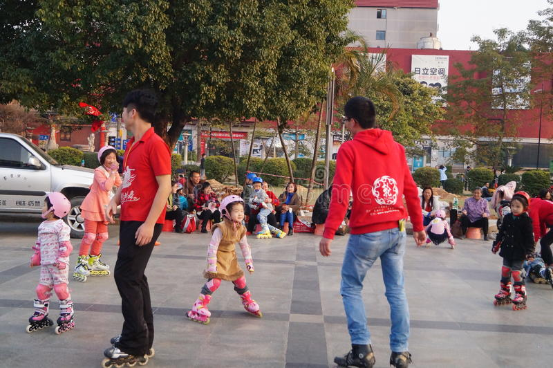 Shenzhen, China: outdoor skating. Shenzhen Baoan Xixiang, outdoor plaza, a little girl and her teacher in skating. This is the recreational sports, people like stock photo