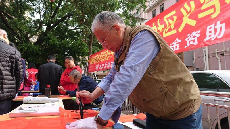Shenzhen, China: quadros superiores aposentados escrevam engates gratuitos no Festival da primavera para residentes em uma comuni imagem de stock royalty free