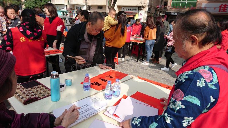 Shenzhen, China: quadros superiores aposentados escrevam engates gratuitos no Festival da primavera para residentes em uma comuni fotos de stock royalty free