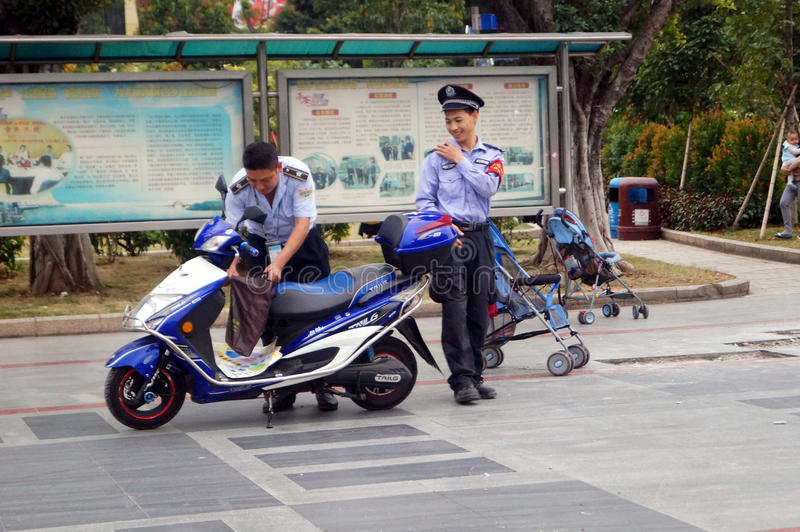 Shenzhen, China: Security Guard members. Shenzhen Xixiang, two security patrol officials and their vehicles royalty free stock photo