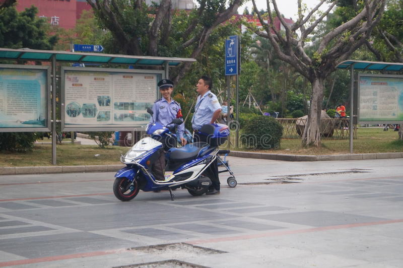 Shenzhen, China: Security Guard members. Shenzhen Xixiang, two security patrol officials and their vehicles stock photos