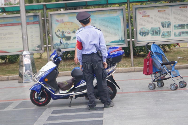 Shenzhen, China: Security Guard members. Shenzhen Xixiang, two security patrol officials and their vehicles stock image