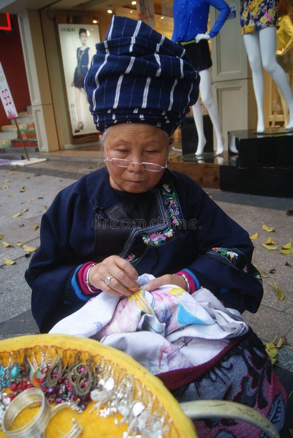 Shenzhen, China: sell Miao silver jewelry. Shenzhen Baoan Xixiang commercial pedestrian street, an old woman in the sale of Miao silver jewelry stock images